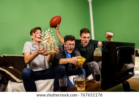Ecstatic family, father and sons cheering for touchdown, while watching american football, funny