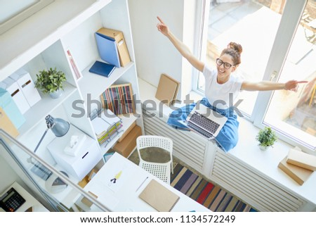 Ecstatic girl with her hands raised sitting on window sill in front of laptop and having fun in office