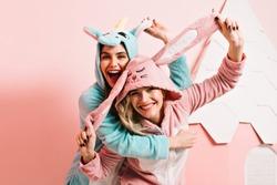 Ecstatic girls in kigurumi fooling around together. Studio shot of inspired young ladies having fun in bedroom.