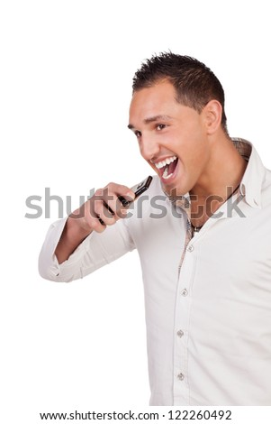 Ecstatic good looking young man holding a mobile and laughing after receiving a call with good news, studio half body portrait isolated on white