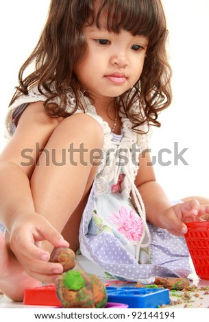 Ecstatic little girl playing with her clay isolated on white background