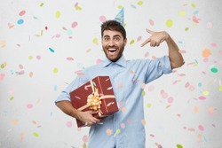 Ecstatic overjoyed young Caucasian man with holiday cap on head holding large box in wrapping paper, feeling excited and euphoric, bragging of his birthday gift, pointing index finger at it
