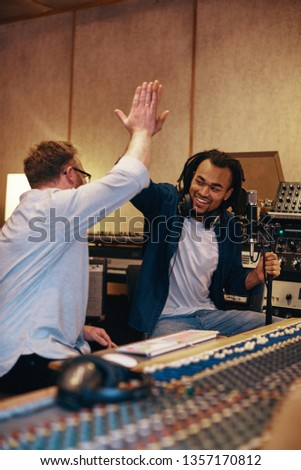 Ecstatic young African American singer high fiving with his music producer after a session in a recording studio #1357170812