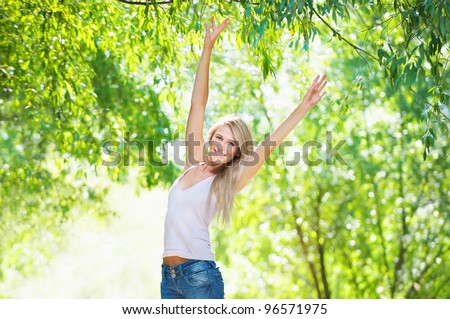 Ecstatic young girl against bright green foliage.