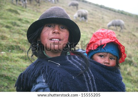 ECUADOR -  SEPTEMBER 02: Girl in traditional clothes carrying a child on her back. Flock of sheep in  background. Great Trekking adventure September 02, 2005 in Ecuador.