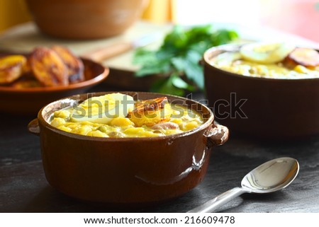 Ecuadorian traditional Easter soup called Fanesca, prepared from many different legumes, gourd, pumpkin, milk and salt cod (Selective Focus, Focus on the front of the egg slice and fried plantain)