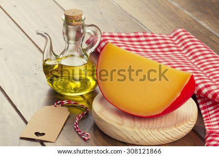 Edam cheese, a red checkered napkin, a tag and olive oil on a wooden table