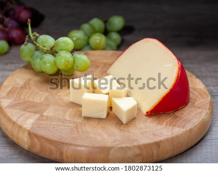 Edam cheese on wooden cutting board with grapes