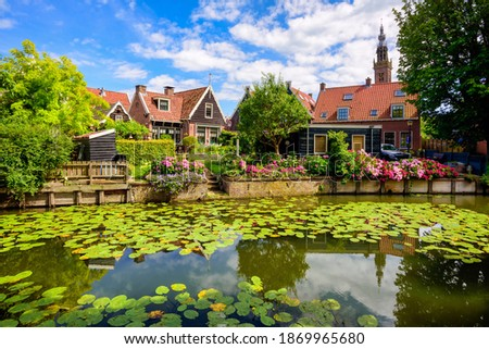 Edam town in North Holland, Netherlands, famous for its Edam cheese, view of traditional stone houses on a river covered with water lilies