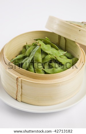Edamame soybeans served warm with salt in bamboo steamer basket