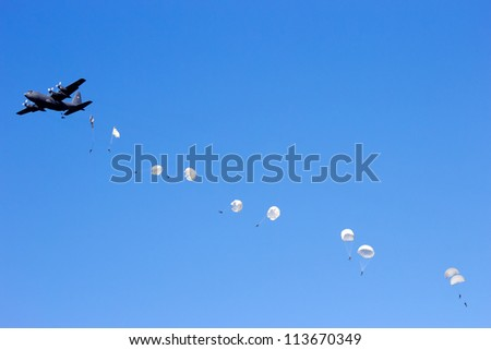 EDE, NETHERLANDS - SEP 22: Polish C-130 Hercules drops para troopers at the Operation Market Garden memorial on Sep 22, 2012 near Ede, Netherlands. Market Garden was a large Allied operation in 1944