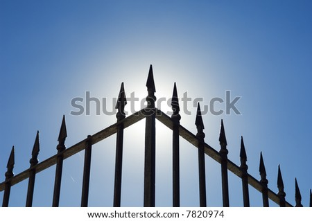 Edge of an old spiked iron railing against the shinning sun.