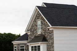 edge of roof shingles on top of the house dark asphalt tiles on the roof background color