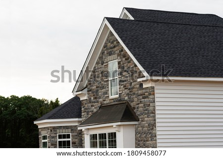 edge of roof shingles on top of the house dark asphalt tiles on the roof background color Stock photo ©