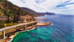 Edge of steep sandscone cliffs along Australian pacific coast with scenic Grand Pacific drive route via Sea Cliff bridge.
