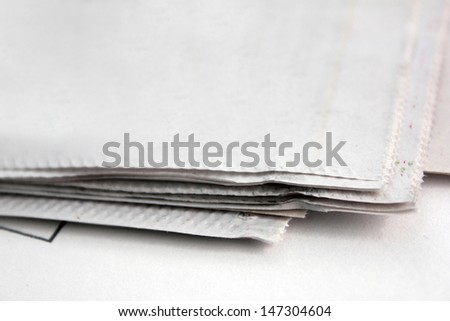 edges of old news paper over white background