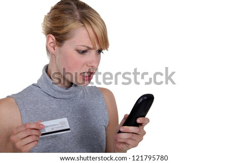 Edgy woman with credit card and telephone