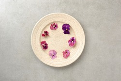 Edible flowers viola in the plate  on the gray background.  Healthy food background. Flat lay in horizontal orientation.