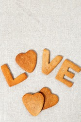 Edible letters of the word love. Shortbread cookies in the form hearts and letters. Vertical format with copy space.
