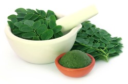 Edible moringa leaves with ground paste over white background