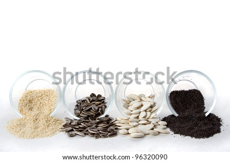 Edible seeds spilling out of glass containers on a white background