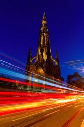 Edinburgh at night scene with Lights streak from high-sided vehicles on Princess street and Scott Monument on background