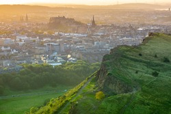 Edinburgh Castle In The Gentle Orange Glow Of A Summer Evening, With Salisbury Crags In The Foreground