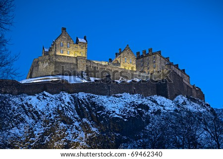Edinburgh Castle, Scotland, UK, illuminated at dusk with winter snow
