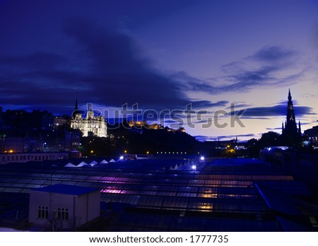 Edinburgh city skyline at dusk with edinburgh castle and bank of scotland floodlit and coloured lighting from waverley railway station in foreground