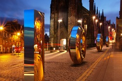 Edinburgh 1000. Cobblestone streets of the Scottish capital. Large shiny numbers of one thousand rolling down castle hill. Logos removed.