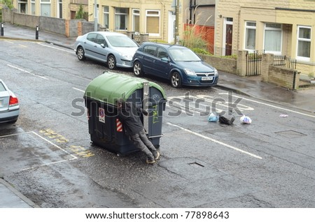 EDINBURGH - MAY 23: An unidentified man removes an upturned rubbish bin on a road that caused a hazard on May 23, 2011 in Edinburgh, Scotland. Winds of up to 100 mph caused havoc across the country and killed two people.