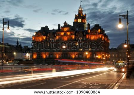 Edinburgh, Scotland - June 16 2015: Balmoral Hotel in Edinburgh, Scotland, at night, with light trails of street bus traffic #1090400864