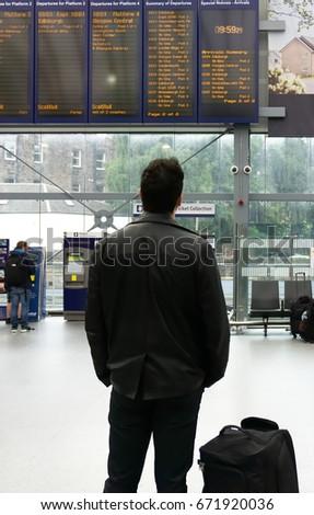EDINBURGH, SCOTLAND - JUNE 20, 2017 : Haymarket Train Station interior showing departure board, unidentified traveller looking at departure board in foreground. #671920036