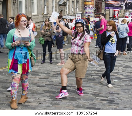 EDINBURGH, UK: AUGUST 2: Unidentified girls hand out flyers on the Royal Mile, the main street of Edinburgh at the Edinburgh Festival Fringe on August 2, 2012 in Edinburgh