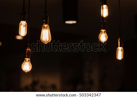 Shutterstock Edison lamps hanging from the ceiling. Vintage style light bulbs decorating room. Loft design background