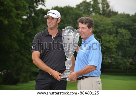 EDISON,NJ-AUGUST 27: Golfer Dustin Johnson (L) holds his winning trophy with Robert Diamond Barclays CEO after winning the Barclays held at the Plainfield Country Club on August 27,2011 in Edison,N.J.