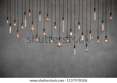 Edison retro lamp Incandescent bulbs on gray plaster wall background in loft. Concept Vintage style. Copy space