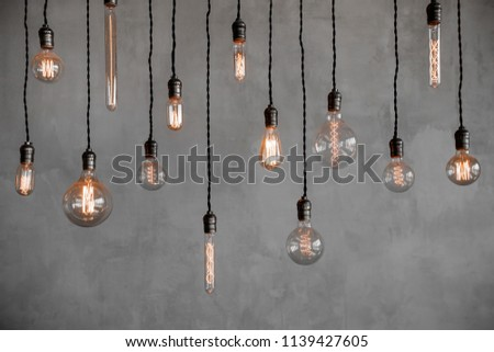 Edison retro lamp Incandescent bulbs on gray plaster wall background in loft. Concept Vintage style