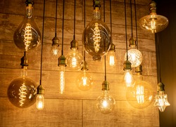 Edison vintage lamps in a glass flask with a tungsten thread inside on a dark background for a modern interior in the house. Assortment in the store. Warm light.