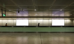 Edited visual for advertising billboard display: Pedestrians walking on moving walkway / travelator in train station. Blank billboards advertising space for mock up purpose; OOH ad placement.