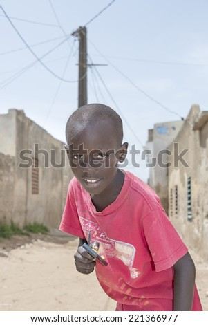 Editorial caption: THIAROYE, SENEGAL, AFRICA  JULY 30, 2014  Unidentified boy standing in the street, popular district of Guinaw Rails