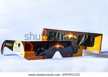 Editorial image of two pairs of solar Lunt Solar Systems eclipse viewing glasses on a white background