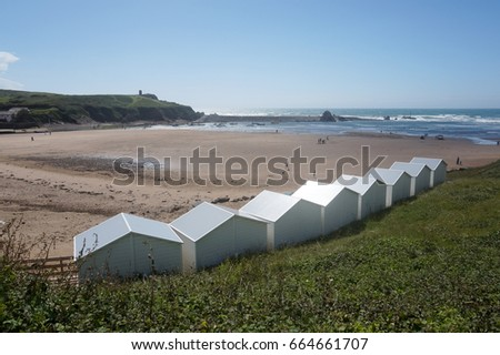 Editorial image of white beach huts with a view over Summerleaze beach and sea at Bude in Cornwall. Taken on 8 June 2017, at Bude Cornwall, United KIngdom. For editorial use only.