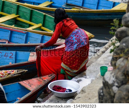 Editorial use only. A nepalese washing clothes at Phewa Lake in Pokhara, Nepal. March 14, 2017