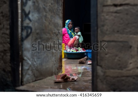 Editorial use. Women work hard from early ages in Africa, taking care of the household and having 4 to 7 children. Image taken in the remote village of Uzi, Zanzibar Island, Tanzania, April 2016.