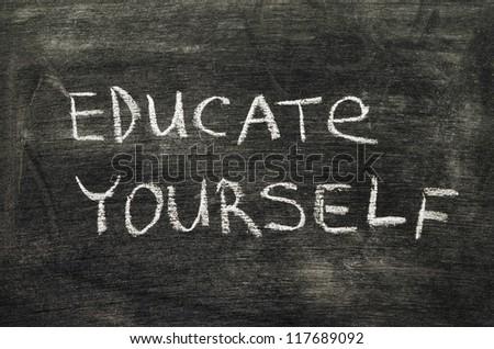 educate yourself phrase handwritten on school blackboard