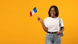 Education abroad, studying in France concept. Positive young black woman student in glasses with backpack holding french flag over yellow studio background, panorama with copy space