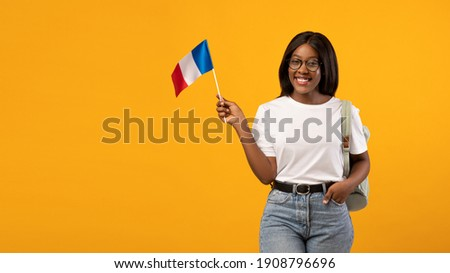 Education abroad, studying in France concept. Positive young black woman student in glasses with backpack holding french flag over yellow studio background, panorama with copy space Photo stock ©