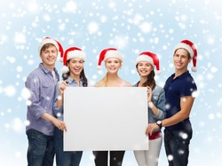 education, advertisement, sale, christmas and people concept - group of smiling students in santa helper hats with blank white board
