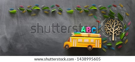 education and back to school concept. Top view photo of school bus and ABC letters, pencils on the roof next to tree with autumn leaves over classroom blackboard background. top view, flat lay
